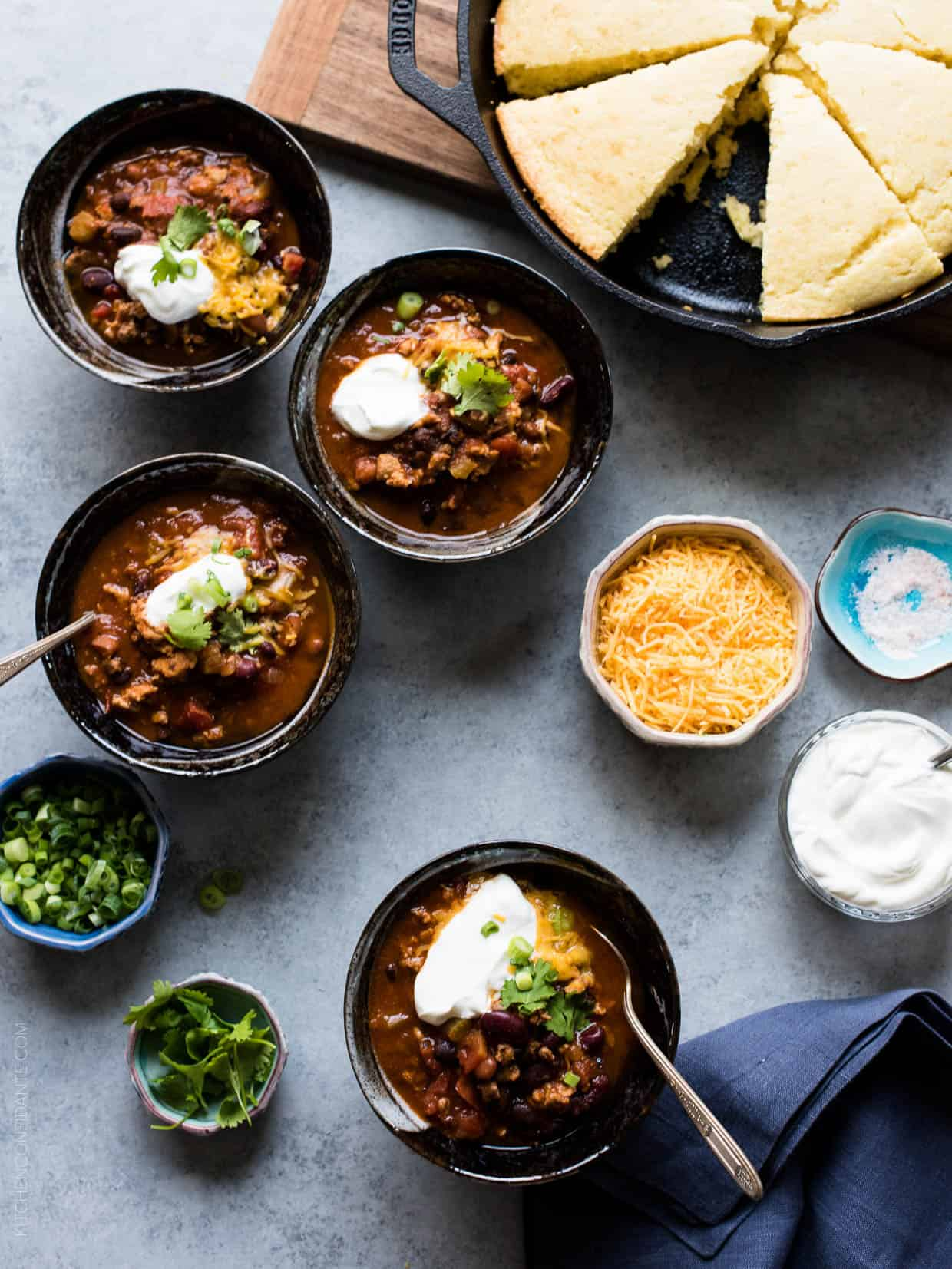 Four bowls of Classic Chili garnished with shredded cheese, sour cream, green onions and cilantro with cornbread muffins in the background.