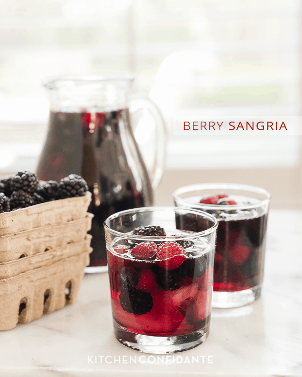 Two glasses filled with bright Berry Sangria and a pitcher with more sangria in the background.