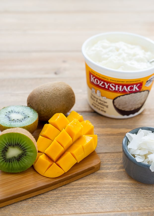 A container of store-bought rice pudding alongside fresh kiwi and mango.