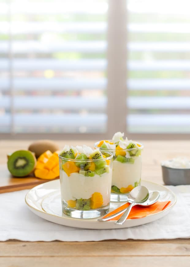 Tropical Rice Pudding layered in glasses with coconut flakes, chopped kiwi and chopped mango.