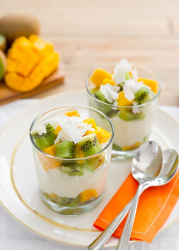 Rice pudding layered in glasses with coconut flakes, chopped kiwi and chopped mango.