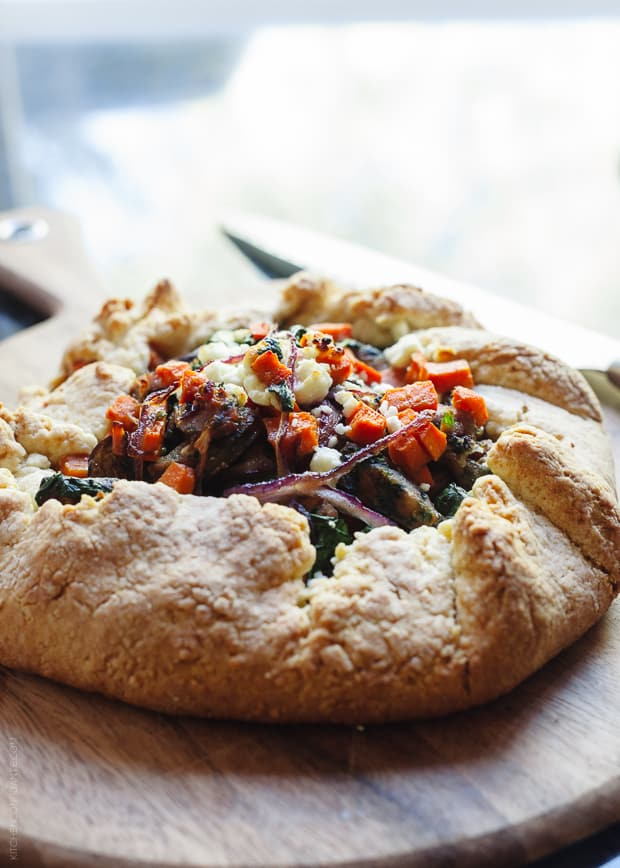 A Savory Chicken Sausage and Vegetable Galette on a wooden serving board.