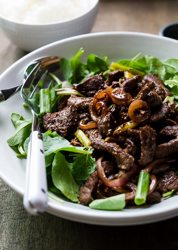 Shaking Beef | www.kitchenconfidante.com | Layers of flavor, with tender beef sirloin and caramelized red onions, served over greens.
