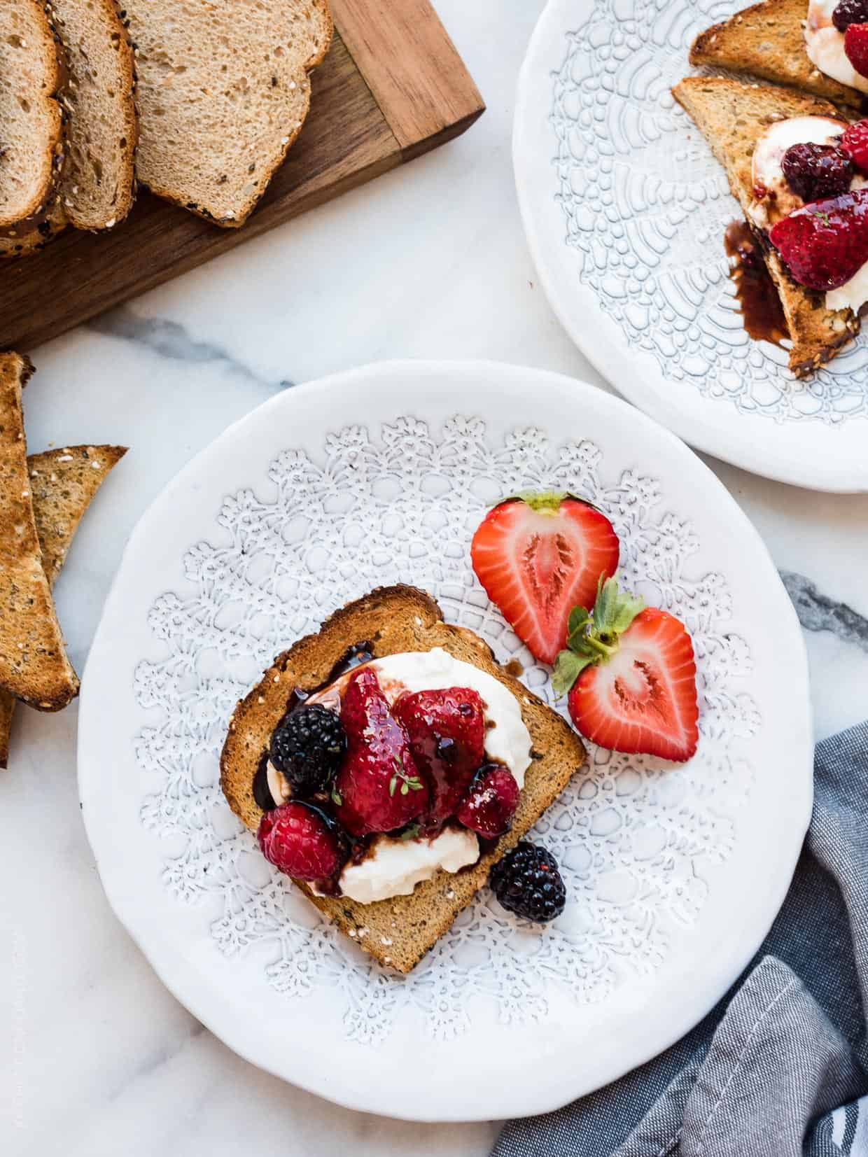 Burrata Toast with Balsamic Berries on a white plate.