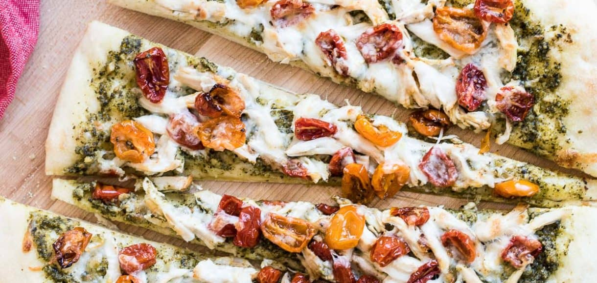 Chicken Pesto Pizza bakes in a snap, thanks to frozen food shortcuts! Make the pizza dough, pesto, chicken and slow-roasted tomatoes in advance, and dinner is ready in minutes. You can even prep and freeze the whole pizza for the busiest of weeknights!