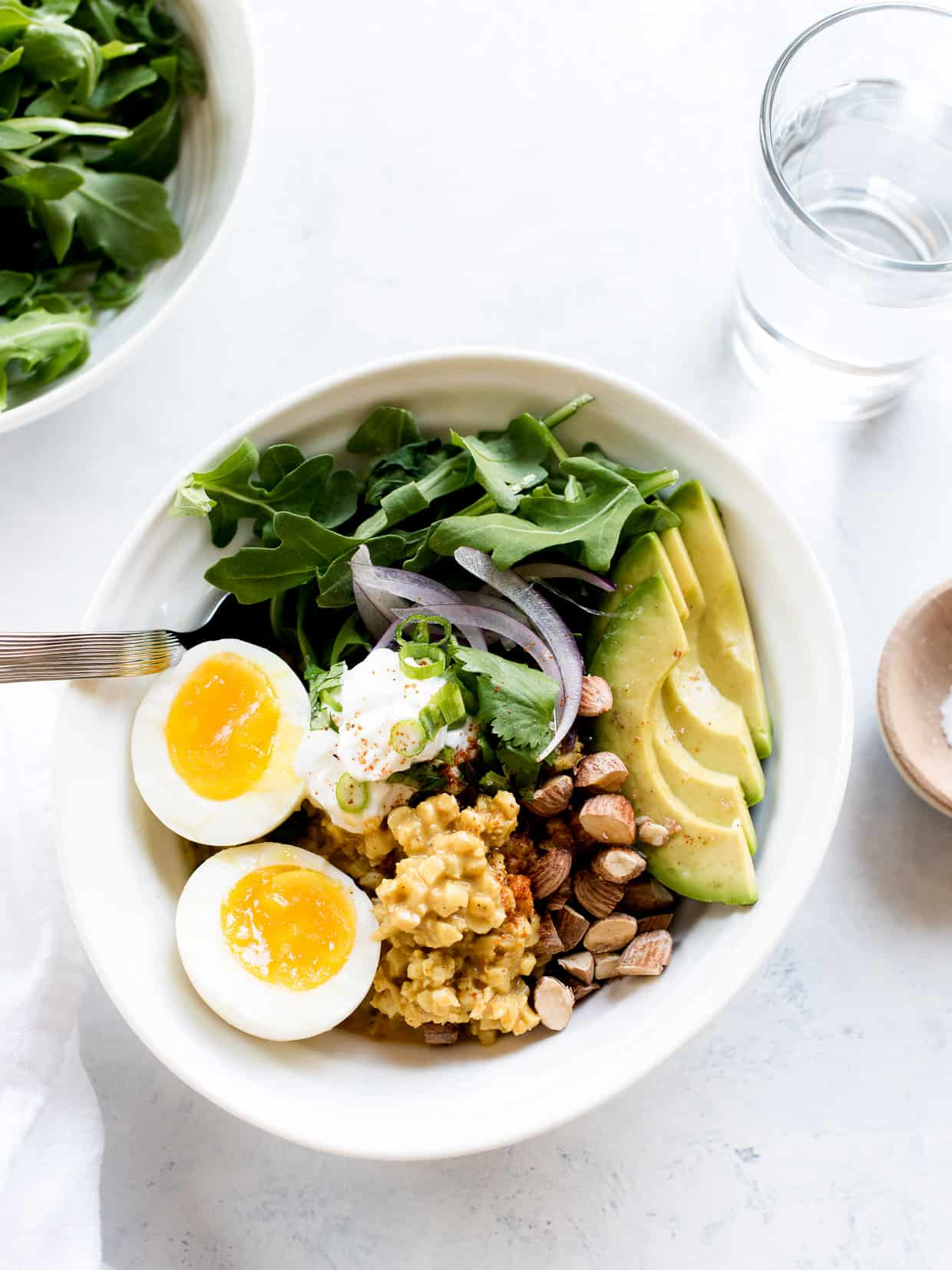 Coconut Curry Cauliflower Rice Bowls topped with eggs, almonds and avocado slices.