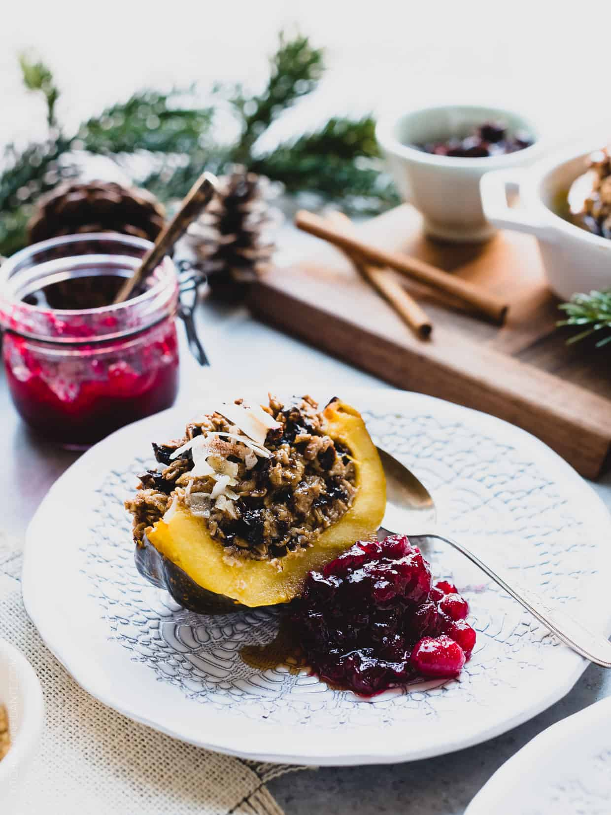 Slice of Baked Oatmeal Stuffed Acorn Squash on a white plate served with cranberry sauce on the side and an additional jar of cranberry sauce in the background.