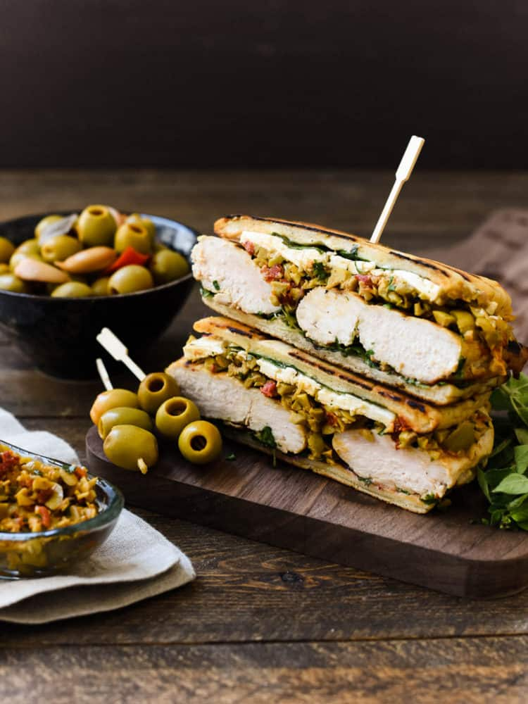 Olive-brined Chicken Sandwich with Olive Tapenade gets its incredible flavor from chicken brined in a Spanish blend olive brine, savory feta cheese, and a hearty spread of olive tapenade. This post is sponsored by Lindsay olives.