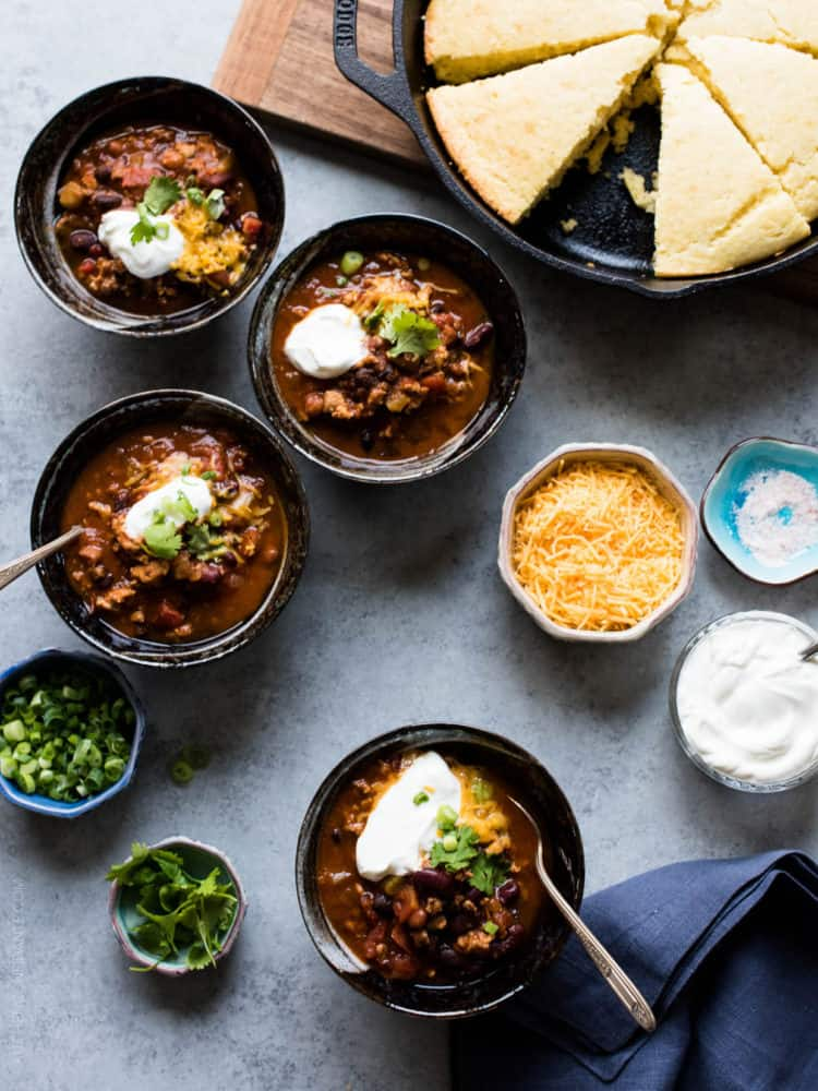 Four bowls of Classic Chili garnished with shredded cheese, sour cream, green onions and cilantro.