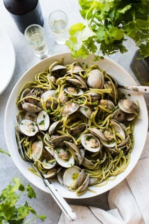 Spinach Linguine with Clams in Sake Red Chili Sauce in a white bowl.