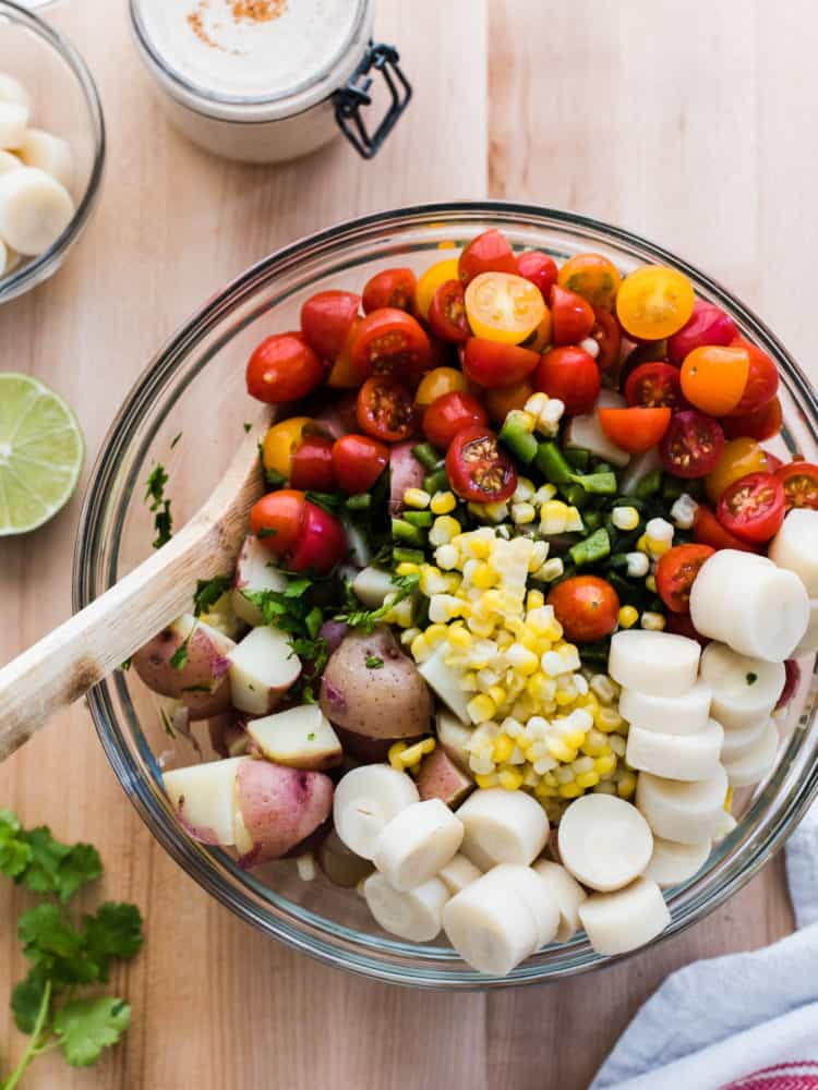 Potatoes, fresh corn, cherry tomatoes and hearts of palm in a glass bowl to make Southwestern Potato Salad