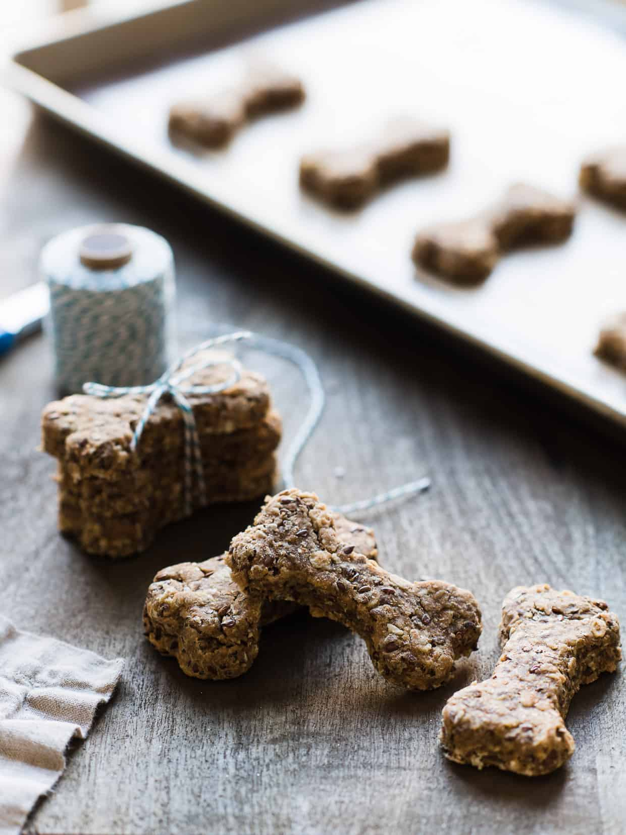 Homemade dog biscuits made with peanut butter, flaxseed and whole wheat flour on a baking sheet.