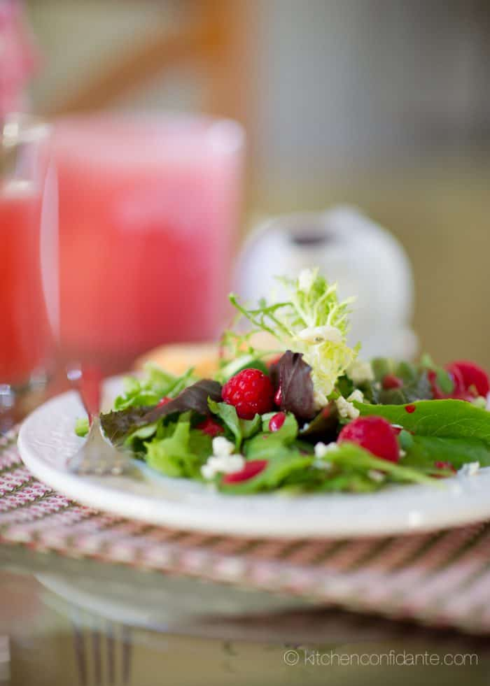 A plate of green salad topped with raspberries, cheese, and homemade raspberry salad dressing.