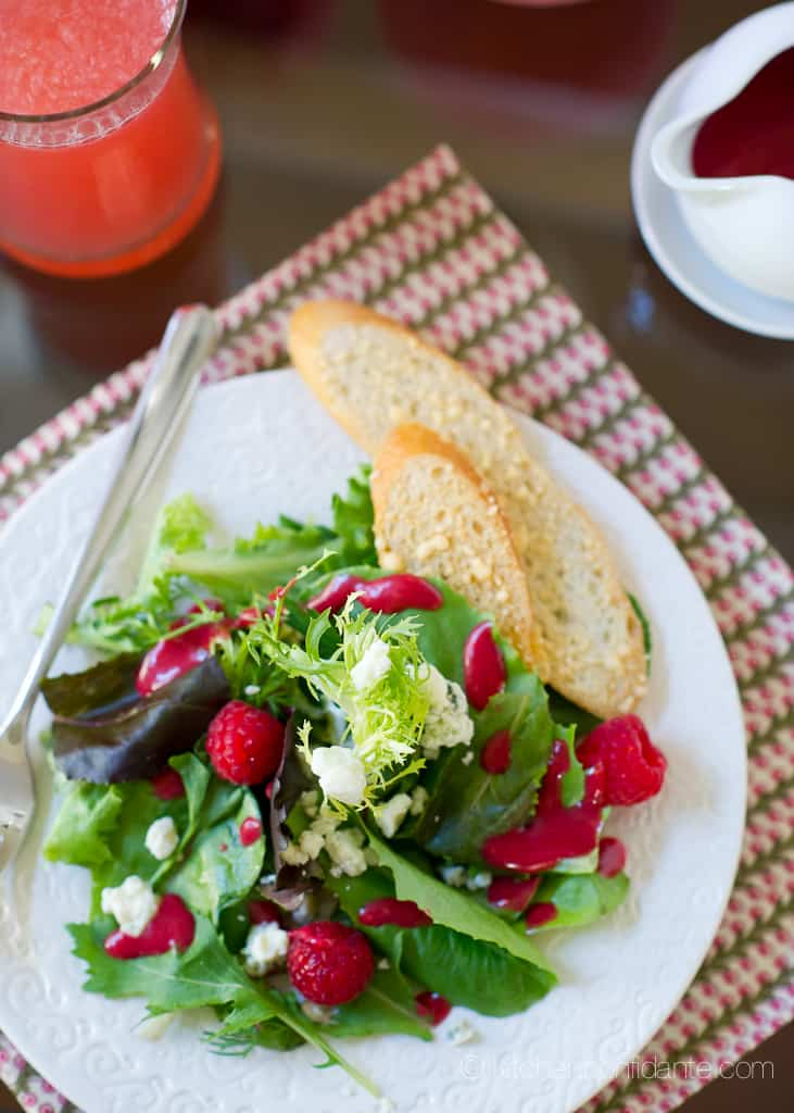 A plate of salad topped with raspberries and served with two slices of bread.