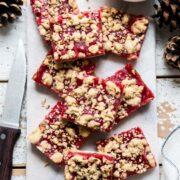 Cranberry Curd and Hazelnut Shortbread Bars on a white marble board lined with parchment paper.