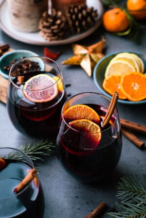 Glasses of mulled wine with citrus, cinnamon, cloves and more spices.