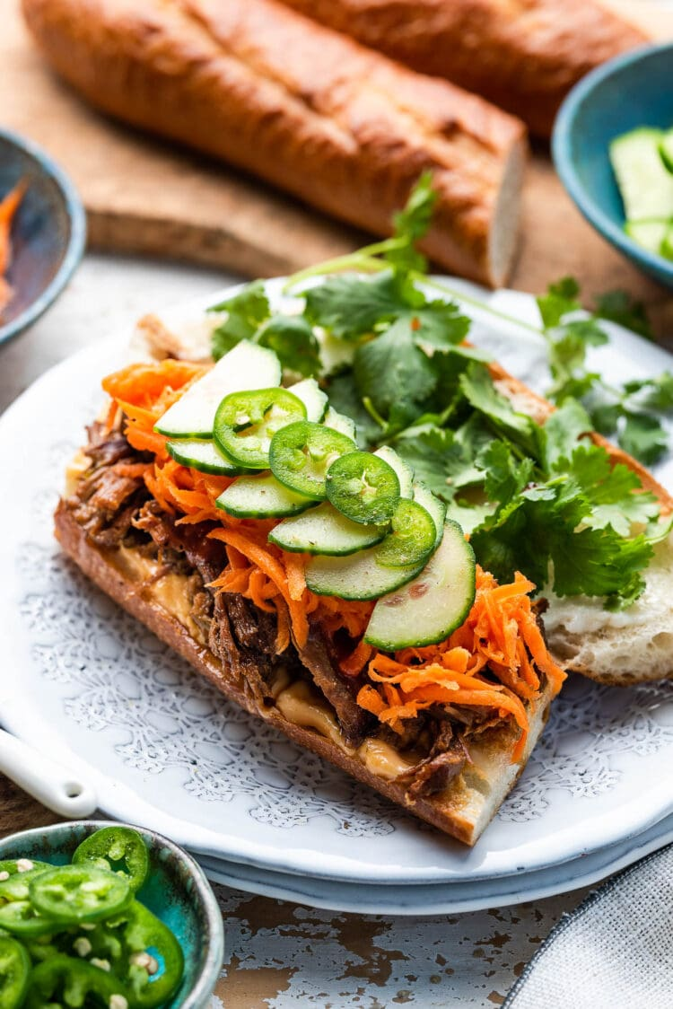 Bahn mi Vietnamese sandwich with pickled carrots, cucumber, jalapenos and cilantro on a French baguette on a white plate.