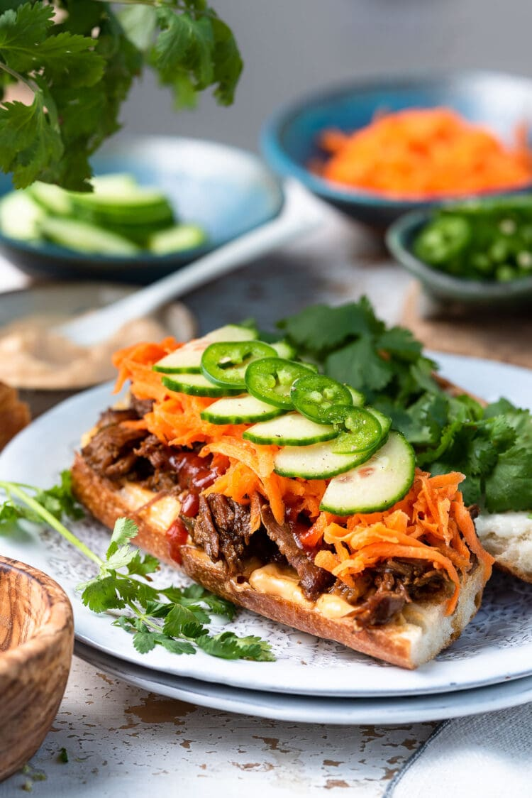 Slow Cooker Bánh Mì Vietnamese Sandwich made with slow cooker pork on a French baguette, topped with pickled carrots, cucumber slices, jalapeno and cilantro on a white plate.