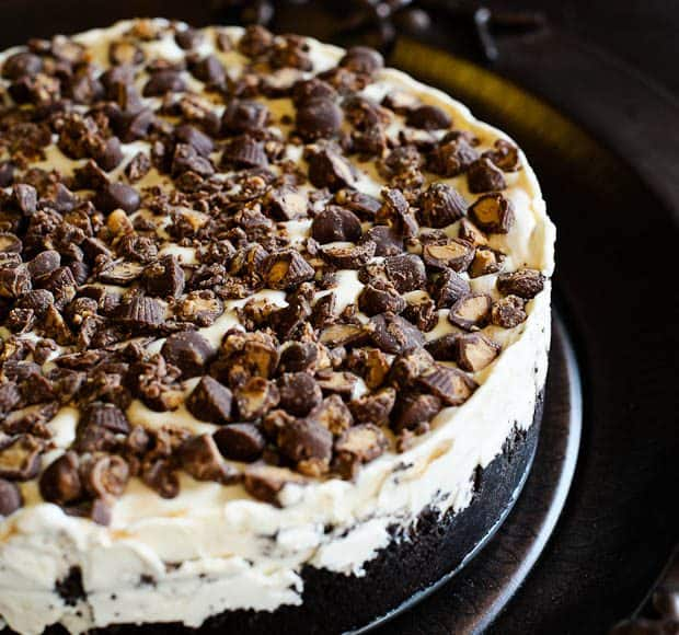 An icebox cake layered with vanilla ice cream and chocolate sandwich cookies and topped with peanut butter cups.