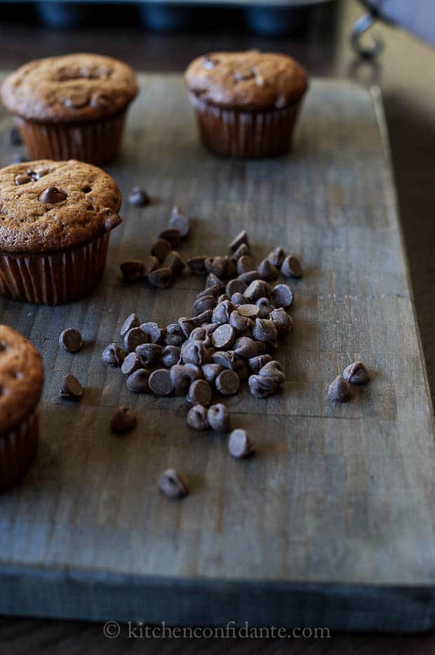 Chocolate banana muffins on a wooden board with scattered chocolate chips