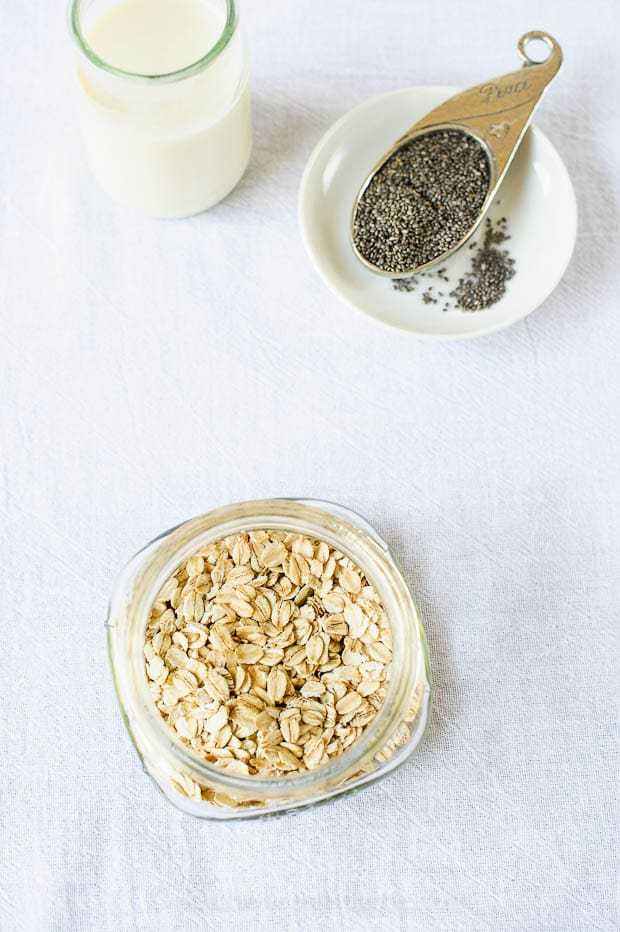 Overhead view of oats in a mason jar, chia seeds in a measuring spoon, and a glass of milk - ingredients for overnight refrigerator oatmeal
