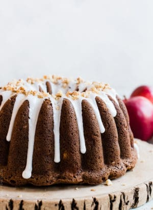 Apple Walnut Delight Cake frosted with glaze and displayed on a wooden serving board.