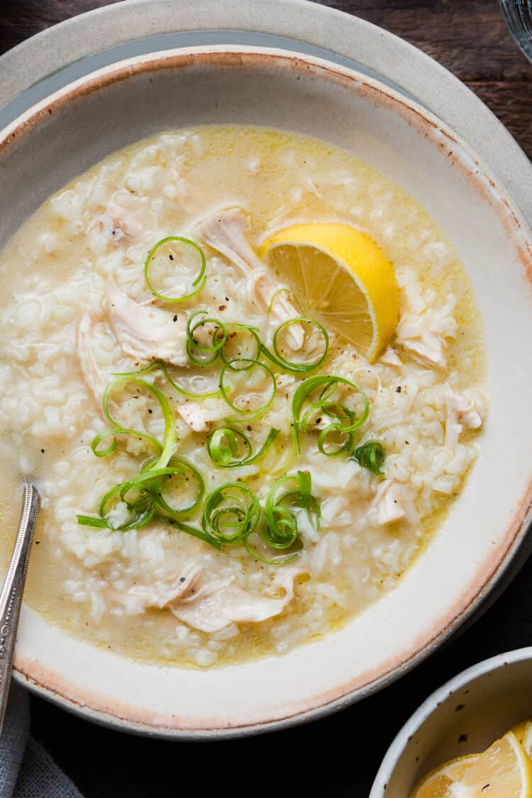 Arroz caldo with garnishes on wood table.