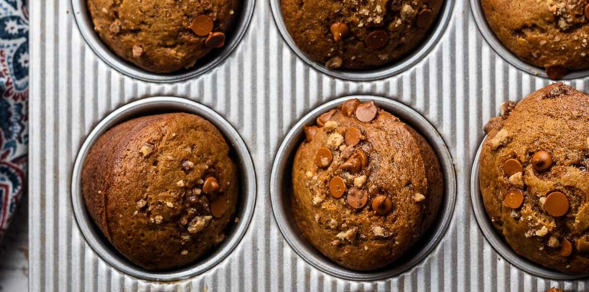 Cinnamon Chip and Walnut Pumpkin Muffins in a muffin pan.