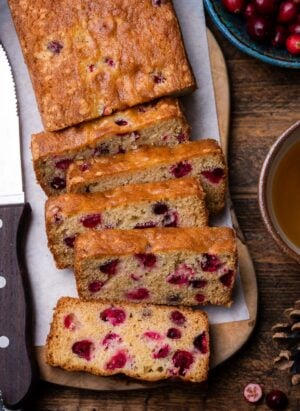 Slices of Fresh Cranberry Tea Cake on a wooden board with a bowl of fresh cranberries to the side.