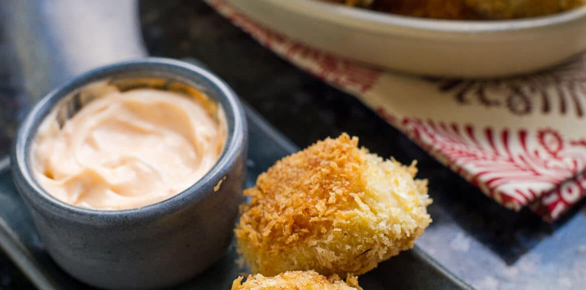 Shrimp and Potato Croquettes on a grey plate with a bowl of Sriracha Mayo.