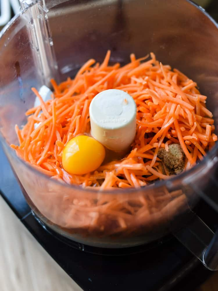 Fresh carrots and ingredients for Carrot Oat Muffins in a food processor.