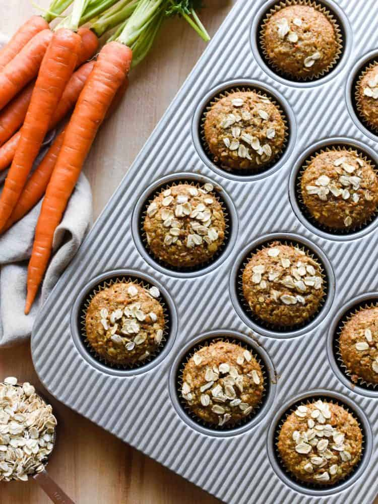 Carrot Oat Muffins in a baking pan with fresh carrots
