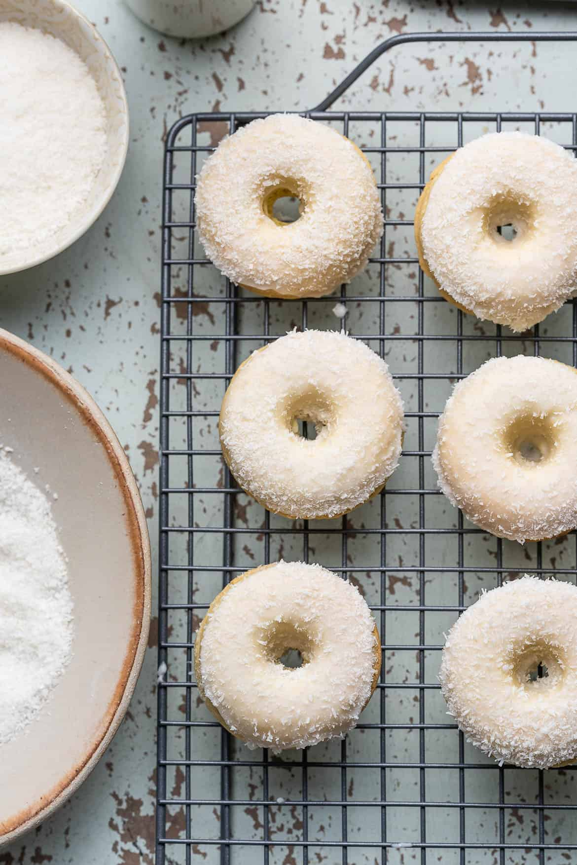 Baked Coconut Doughnuts on a wire cooling rack.