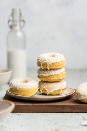 Stack of baked coconut doughnuts on a plate with coconut milk.