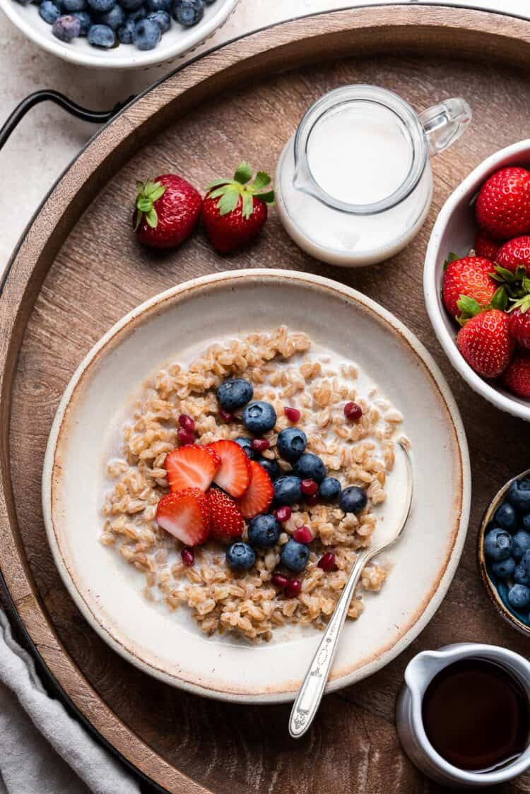 Farro Breakfast porridge in a bowl topped with blueberries and strawberries.