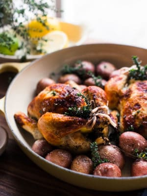 Roasted buttermilk brined cornish hens in yellow roasting pan with red potatoes.
