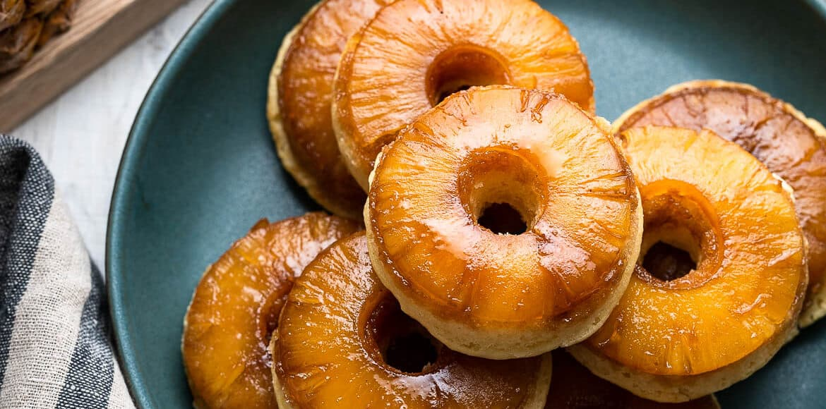 Pineapple Upside Down Cake Doughnuts stacked on a green plate.
