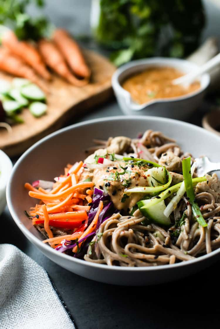 Soba Noodles and Chicken with Spicy Peanut Sauce topped with fresh vegetables in a bowl.