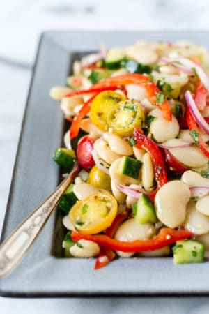 Lima Bean Salad on a serving dish with cucumbers, tomatoes and red bell peppers.