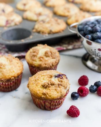 Freshly baked mixed berry muffins with summer berries surrounding them on a countertop.