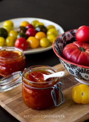 Tomato Jam in a glass jar surrounded by fresh tomatoes.
