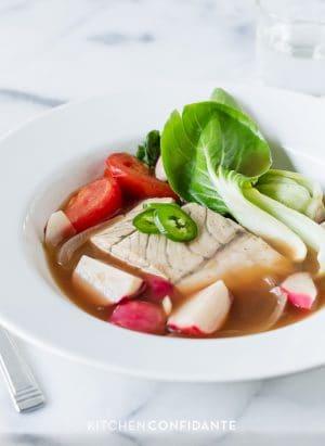 Barramundi Fish in Tamarind Broth (Sinigang na Isda) served in a white bowl.
