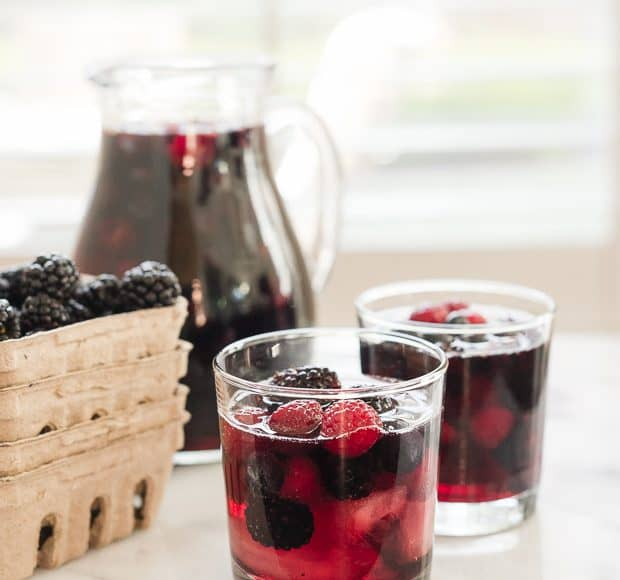 Glasses of Berry Sangria filled with bright red and blue summer berries.