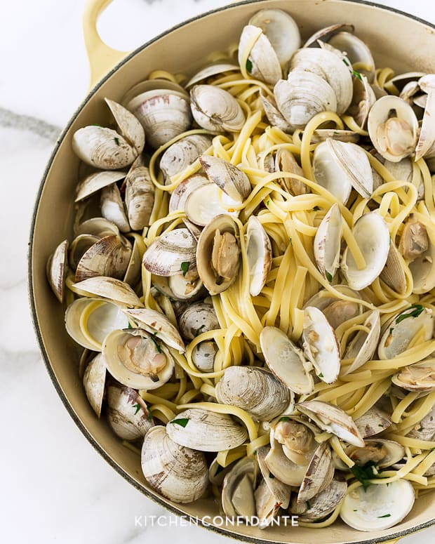 Opened clams on a bed of linguine and white wine sauce in a large pot.