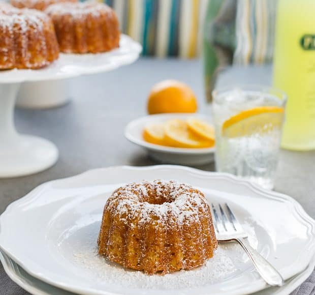 Mini lemon Bundt sprinkled with confectioner's sugar and served on a white plate.