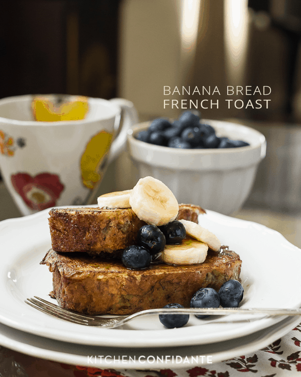 Two slices of Banana Bread French Toast topped with blueberries, sliced bananas and maple syrup.