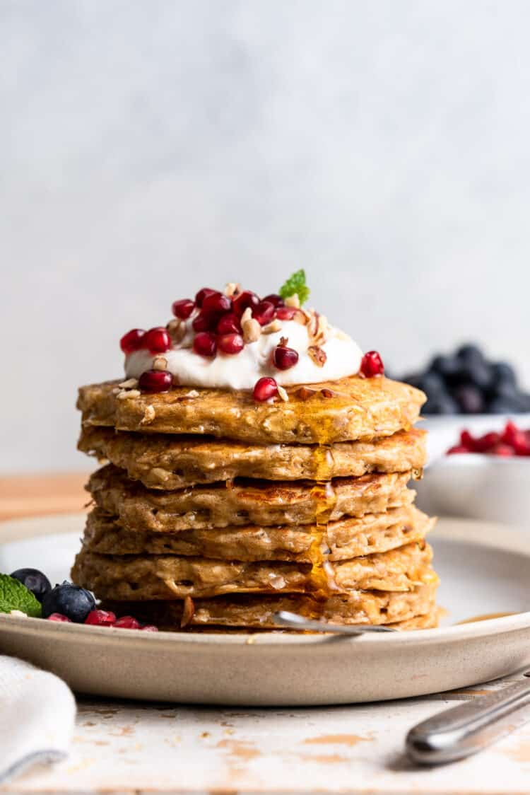 Oatmeal Pancakes stacked on a plate, topped with whipped cream, pomegranate seeds, nuts and maple syrup.