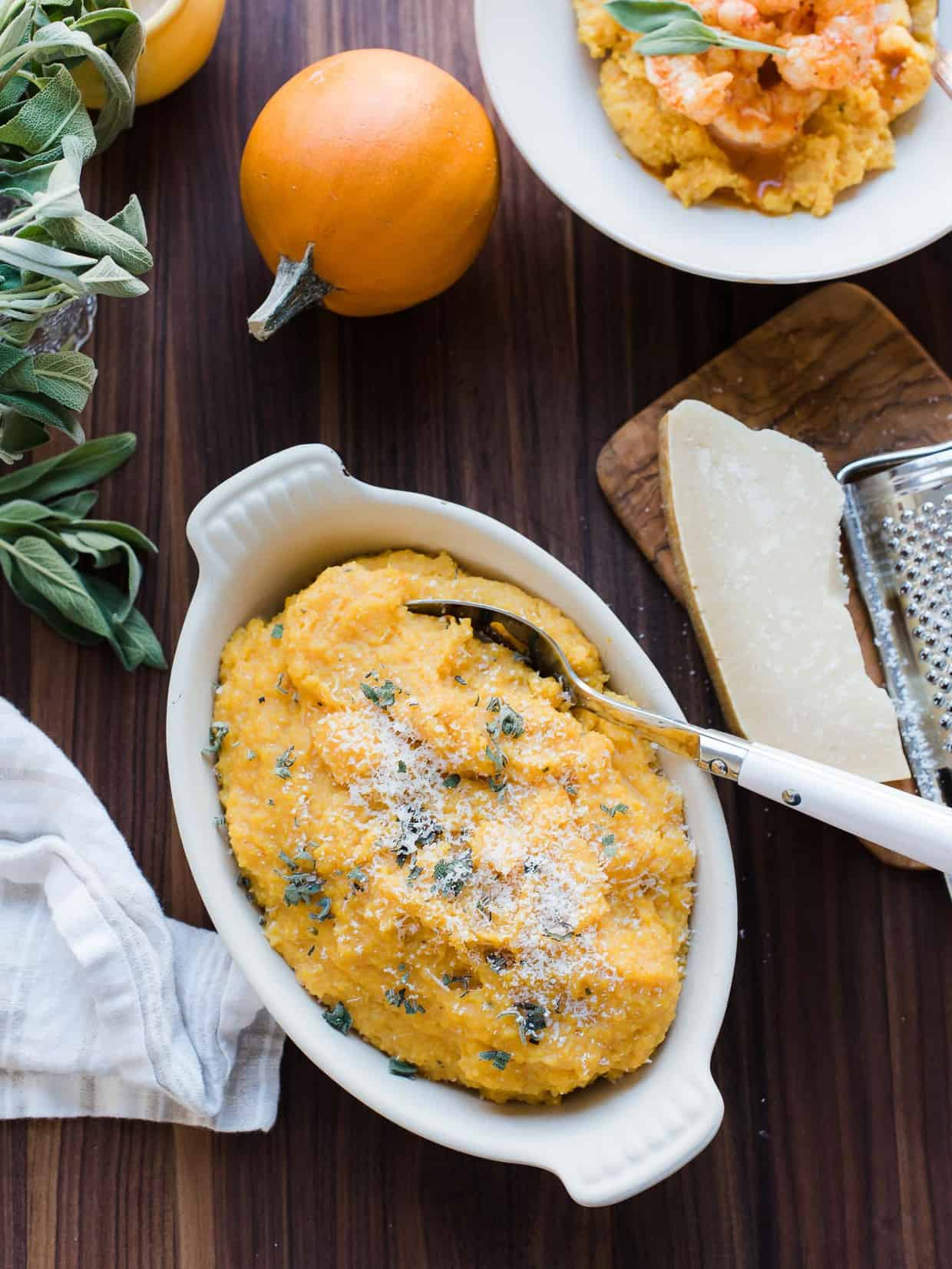 A white serving bowl filled with Pumpkin Sage Polenta surrounded by fresh sage and pumpkins.