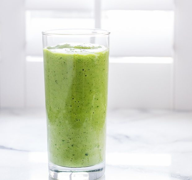 Mango Spinach Green Smoothie against a white background