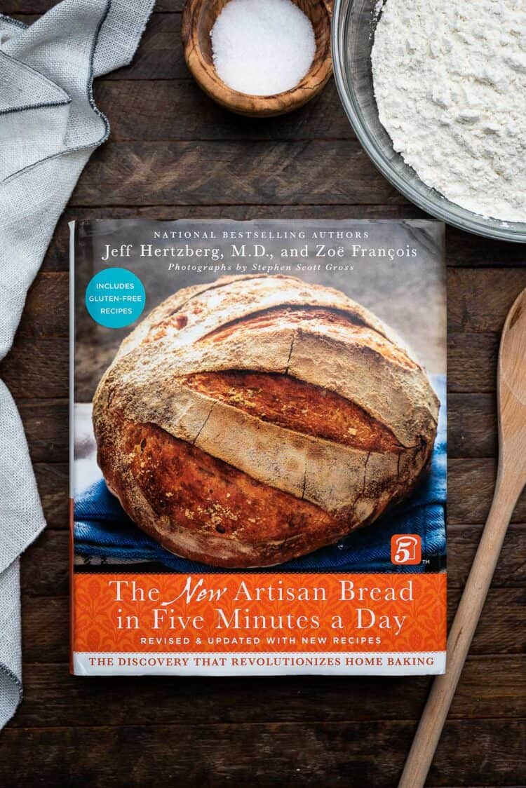 The New Artisan Bread in Five Minutes a Day cookbook on a wooden table.